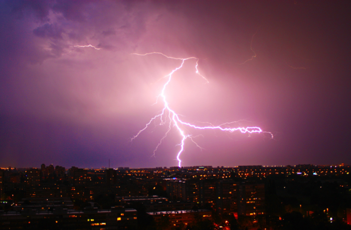 A violet sky is lit by a gigantic thunderbolt striking a city.